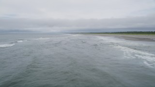 AX56_121 - 5K stock footage aerial video fly low over waves rolling toward an empty beach in Ilwaco, Washington