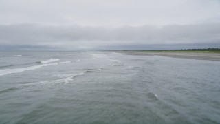 AX56_122 - 5K stock footage aerial video of flying low over small waves rolling in to an empty beach in Ilwaco, Washington