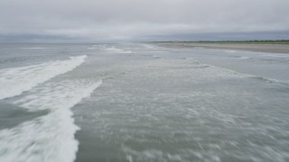 AX56_123 - 5K stock footage aerial video of low altitude flight over ocean waves near an empty beach in Ilwaco, Washington