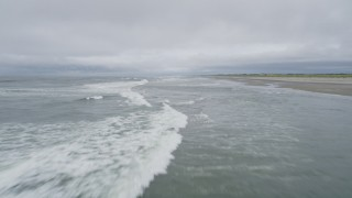 AX56_125 - 5K stock footage aerial video of a low altitude flight over crashing waves near an empty beach in Ilwaco, Washington