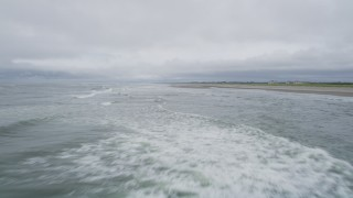 AX56_126 - 5K stock footage aerial video of low flight over crashing waves near an empty beach in Seaview, Washington
