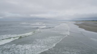 AX56_127 - 5K stock footage aerial video of crashing ocean waves near an empty beach in Seaview, Washington