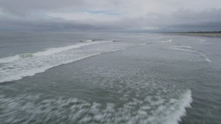 AX56_129 - 5K stock footage aerial video of crashing waves near a beach in Seaview, Washington