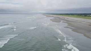 AX56_132 - 5K stock footage aerial video fly over waves rolling in near a beachgoer on the sand in Seaview, Washington