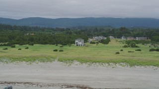 AX56_133 - 5K stock footage aerial video of homes and green fields near the beach in Long Beach, Washington