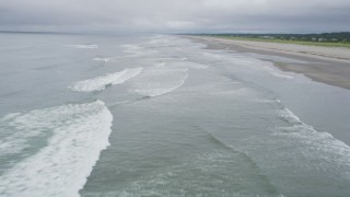 AX56_134 - 5K stock footage aerial video fly over ocean waves near the beach, and pan toward the Pacific Ocean, Long Beach, Washington