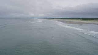 AX56_137 - 5K stock footage aerial video of ocean waves rolling toward a beach with a few people on the shore in Long Beach, Washington