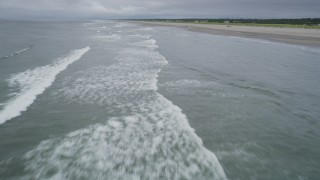 AX56_139 - 5K stock footage aerial video fly over waves crashing near people enjoying the beach in Long Beach, Washington