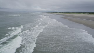 AX56_140 - 5K stock footage aerial video of a low altitude flight over ocean waves near an empty beach in Long Beach, Washington