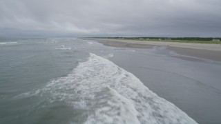 AX56_141 - 5K stock footage aerial video fly low over ocean waves and an empty beach in Long Beach, Washington