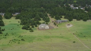 AX56_144 - 5K stock footage aerial video of rural homes with trees, green fields in Oceanside, Washington