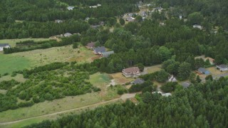 AX56_145 - 5K stock footage aerial video approach rural homes and trees in Oceanside, Washington
