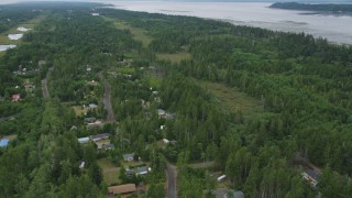 AX56_147 - 5K stock footage aerial video of rural neighborhood nearly hidden by evergreens near Willapa Bay, Oceanside, Washington