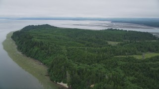 AX56_149 - 5K stock footage aerial video fly over green shore and evergreen forest on Long Island, Washington