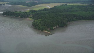 AX56_155 - 5K stock footage aerial video of evergreen forest and wetlands on the shore of Willapa Bay, Nemah, Washington