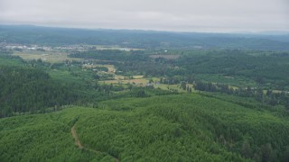 AX56_171 - 5K stock footage aerial video of approaching small farms from evergreen forest in Raymond, Washington