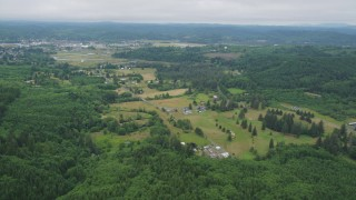 AX56_172 - 5K stock footage aerial video approach small farms from the forest near the town of Raymond, Washington