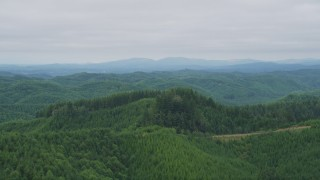 AX57_002 - 5K stock footage aerial video approach hills covered by evergreen forest in Satsop, Washington