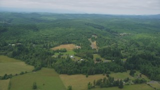 AX57_018 - 5K stock footage aerial video fly over farm fields to approach a small farm and evergreen forest in Satsop, Washington