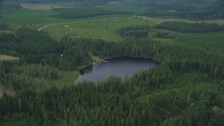 AX57_031 - 5K stock footage aerial video of forest surrounding Panhandle Lake and a campground with docks in Shelton, Washington