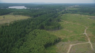 AX58_012 - 5K stock footage aerial video tilt from railroad tracks through trees to dirt roads through a logging area in Grapeview, Washington