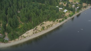 AX58_025 - 5K stock footage aerial video fly over empty beach and waterfront homes on the shore of the Case Inlet in Vaughn, Washington