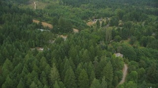 AX58_026 - 5K stock footage aerial video fly over rural homes and evergreen forest by a road in Vaughn, Washington