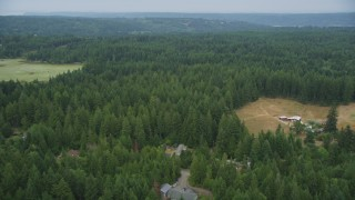 AX58_049 - 5K stock footage aerial video fly over evergreen forest and reveal rural homes in Olalla, Washington