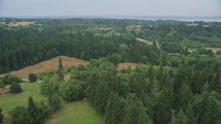 AX58_059 - 5K stock footage aerial video fly over livestock in a pasture to approach small farms on Vashon Island, Washington