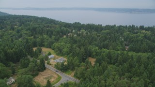 AX58_062 - 5K stock footage aerial video fly over small farms and rural homes on the way to the shore of Vashon Island, Washington
