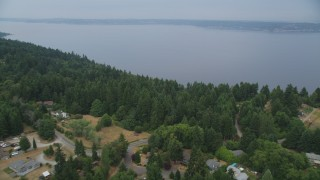 AX58_063 - 5K stock footage aerial video fly over rural homes and the island shore toward Puget Sound, Vashon Island, Washington