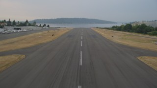 AX58_083 - 5K stock footage aerial video fly over the runway and landing at Renton Municipal Airport, Renton, Washington