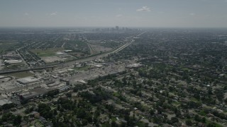 AX59_001 - 5K stock footage aerial video fly over Gentilly to approach stores by the I-10, with Downtown New Orleans in the background, Louisiana