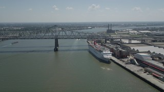 AX59_043 - 5K stock footage aerial video of cruise ship docked beside the Crescent City Connection Bridge, New Orleans, Louisiana