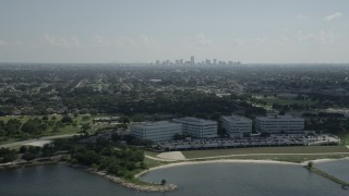 AX60_002 - 5K stock footage aerial video of office buildings by Lake Pontchartrain, and view of Downtown New Orleans skyline, Louisiana