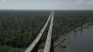 AX60_008 - 5K stock footage aerial video track light traffic on Interstate 10, and ascend to a wider view of the freeway and swampland in Norco and LaPlace, Louisiana