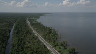 AX60_009 - 5K stock footage aerial video of railroad tracks through swampland on the lakeshore in La Place, Louisiana