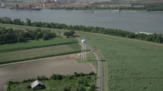AX60_030 - 5K stock footage aerial video of a water tower beside a country road and crop fields in Wallace, Louisiana