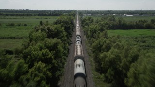 AX60_060 - 5K stock footage aerial video follow railroad tracks to approach and fly over a train in Vacherie, Louisiana