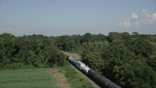 AX60_064 - 5K stock footage aerial video track a train traveling past sugar cane fields and over a country road in Vacherie, Louisiana