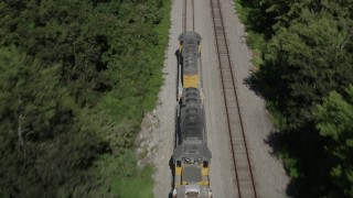 AX60_066 - 5K stock footage aerial video tilt and track the engine of a train running between trees in Edgard, Louisiana