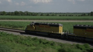 AX60_067 - 5K stock footage aerial video of tracking a train speeding past sugar cane fields, Edgard, Louisiana