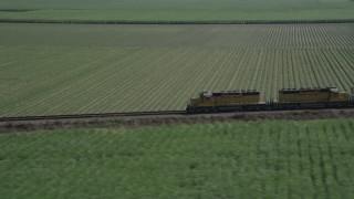 AX60_069 - 5K stock footage aerial video track a train passing by sugar cane fields, Edgard, Louisiana