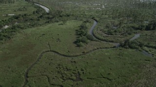 AX60_086 - 5K stock footage aerial video tilt from a bird's eye view of a river and fly over swampland in St. Charles Parish, Louisiana