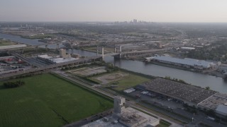 AX61_002 - 5K stock footage aerial video fly over warehouse buildings to approach Danziger Bridge at sunset, New Orleans, Louisiana