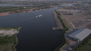 AX61_004 - 5K stock footage aerial video approach a barge sailing on Industrial Canal at sunset, New Orleans, Louisiana