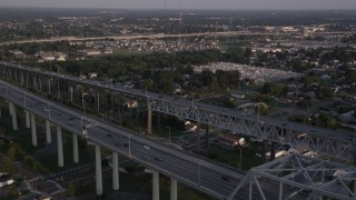 AX61_020 - 5K stock footage aerial video fly over the convention center to track cars on Crescent City Connection Bridge at sunset, New Orleans, Louisiana