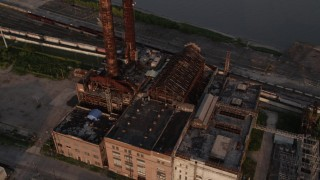 AX61_023 - 5K stock footage aerial video old power plant on bank of Mississippi River at sunset, New Orleans, Louisiana