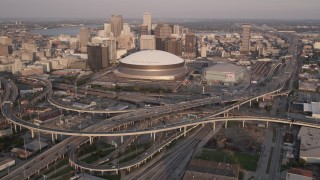 AX61_029 - 5K stock footage aerial video reverse view of Superdome and Downtown New Orleans skyscrapers at sunset, Louisiana