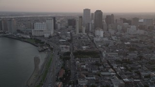 AX61_050 - 5K stock footage aerial video of Downtown New Orleans at sunset, seen from the French Quarter and the Mississippi River, Louisiana